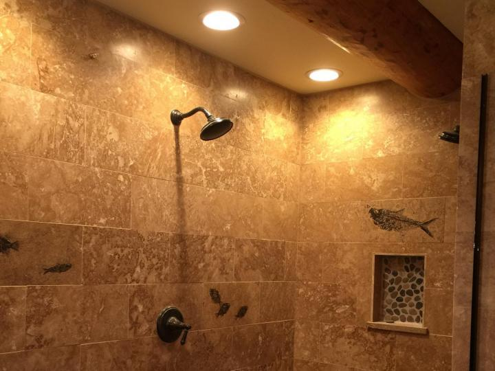 custom tile shower with can lights in ceiling.